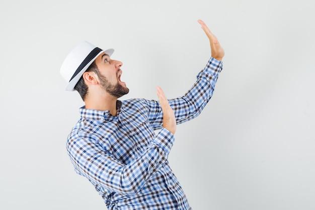 Giovane maschio mantenendo le mani in modo preventivo in camicia a quadri, cappello e guardando spaventato. vista frontale. Foto Gratuite