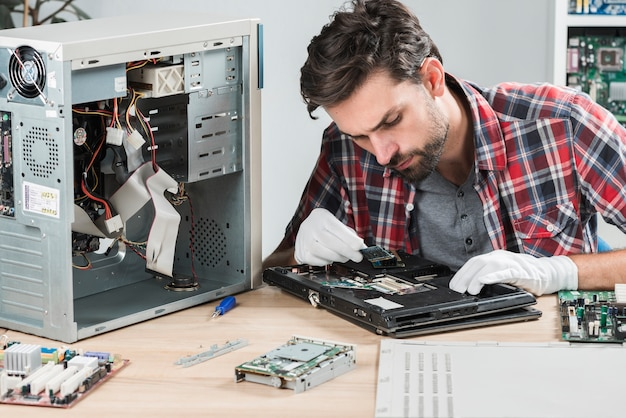 Young male looking at laptop ram on wooden desk Premium Photo