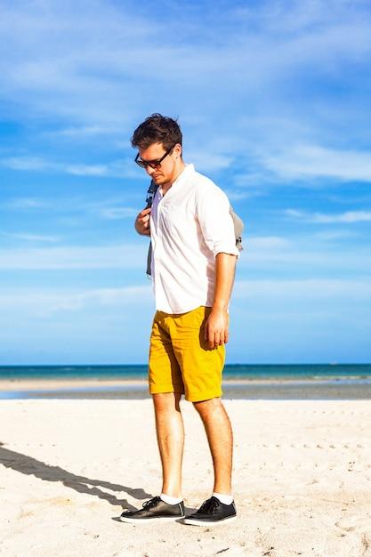 スタイリッシュなバックパックで海のそばで夏休みを楽しむ若い男性モデル 無料写真