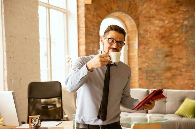 Молодой мужской офисный работник, пить кофе в офисе Бесплатные Фотографии