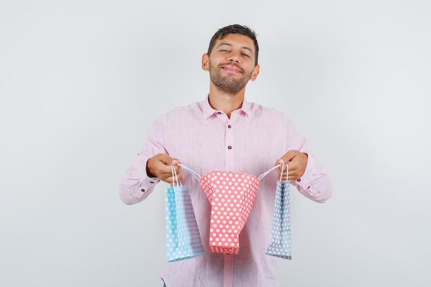 젊은 남성 셔츠에 종이 가방을 열고 기쁜, 전면보기를 찾고. 무료 사진