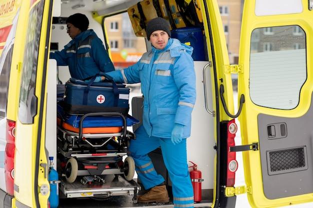 救急車のドアの担架のそばに立ってまっすぐ見ている救急箱を持った若い男性救急隊員 Premium写真