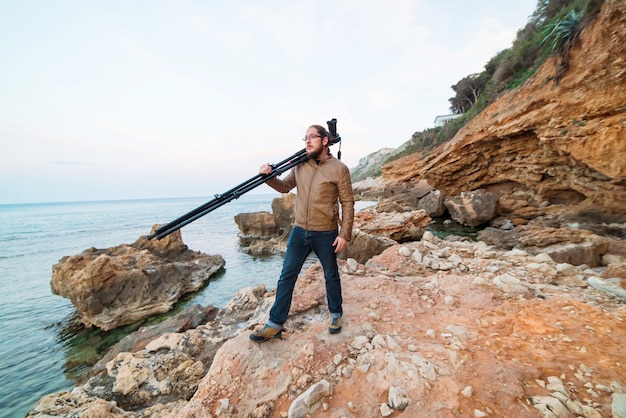 Young male photographer standing on rock with camera on tripod and looking into the sea Premium Photo