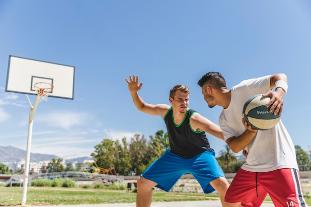 Young male player playing with basketball player Free Photo