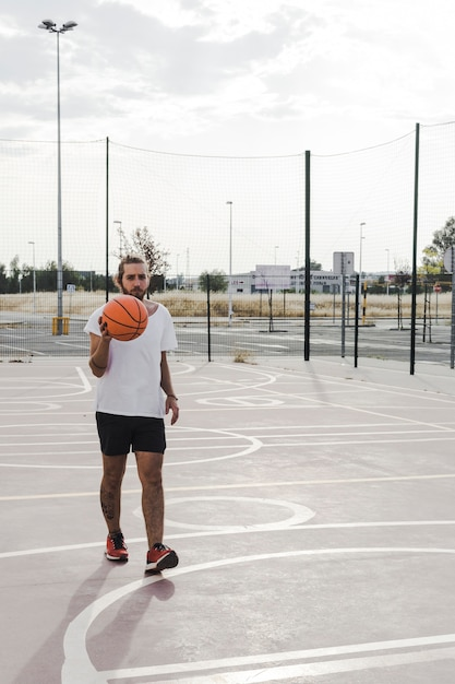 Young male player with basketball in court Free Photo