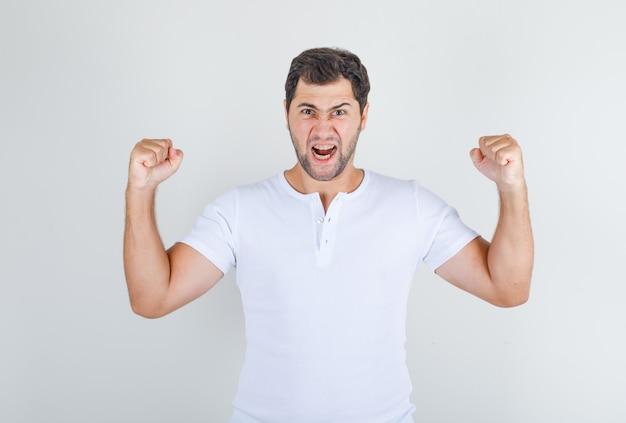 Giovane maschio che grida ad alta voce con i pugni chiusi in maglietta bianca e sembra emotivo Foto Gratuite