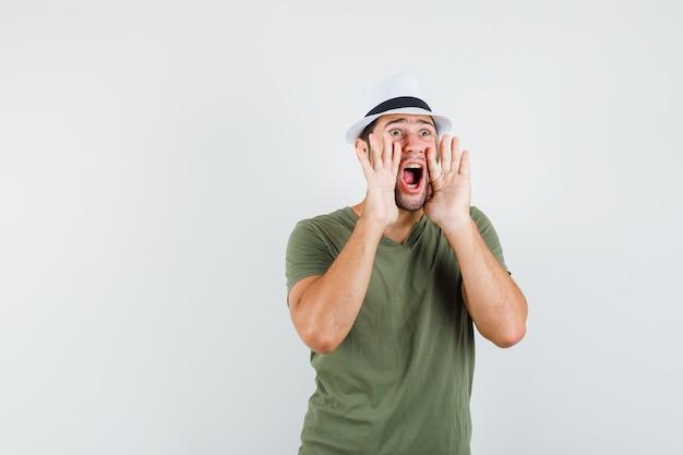 緑のtシャツと帽子の正面図で何かを叫んだり発表したりする若い男性。 無料写真