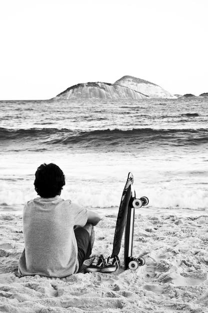 Giovane maschio seduto su una spiaggia e ammirando il mare Foto Gratuite