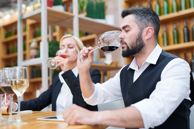 Young male sommelier smelling red wine in bokal with his coleague tasting beverage Premium Photo