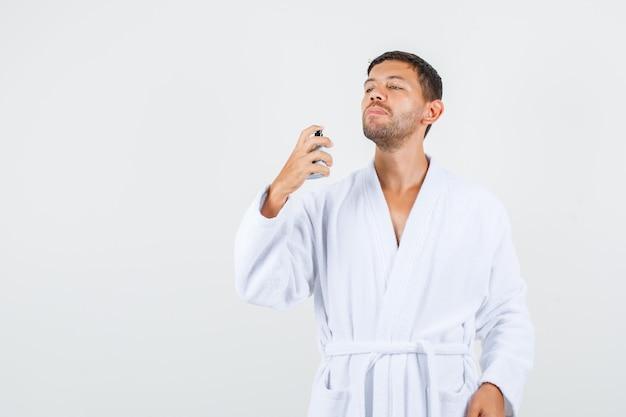 若い男性が白いバスローブに香水をスプレーし、自信を持って、正面図を探しています。 無料写真