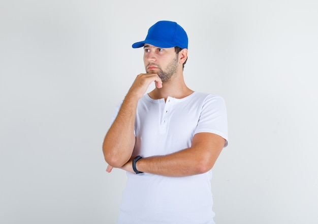 白いtシャツと青い帽子のあごに手で立っている若い男性 無料写真