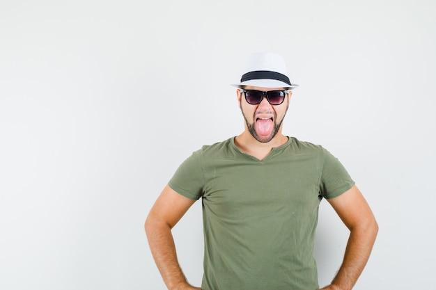 緑のtシャツと帽子で舌を突き出して狂ったように見える若い男性 無料写真
