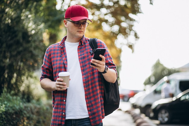 Young male student drinking coffee using phone in park Free Photo