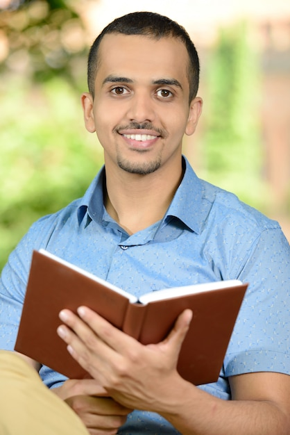 Young male student reading a book outdoors in park. Premium Photo