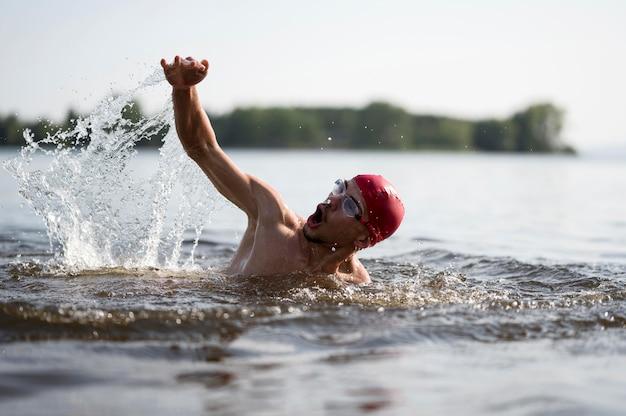 Giovane maschio che nuota nel lago Foto Gratuite