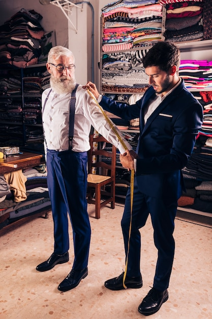 Young male tailor taking measurement of senior man's sleeves in the shop Free Photo