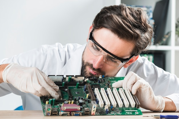 Young male technician inserting chip in computer motherboard on wooden desk Free Photo