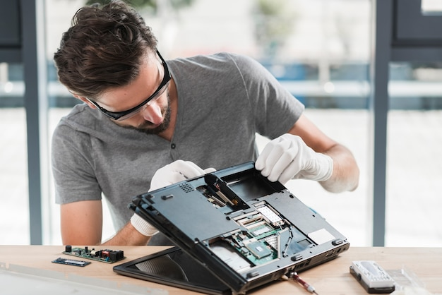 Young male technician repairing laptop on wooden desk Free Photo