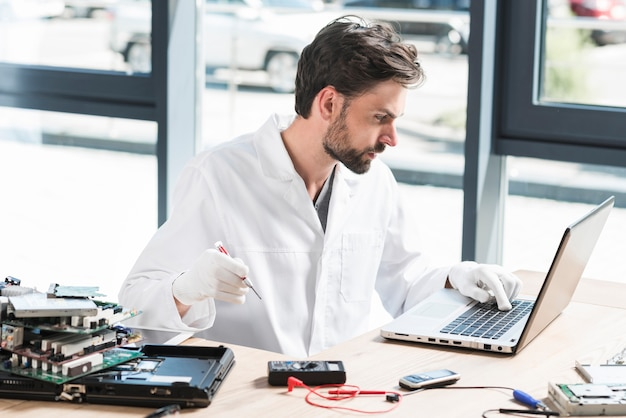 Young male technician using laptop in workshop Free Photo