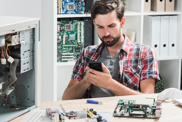 Young male technician using mobile phone in workshop Free Photo