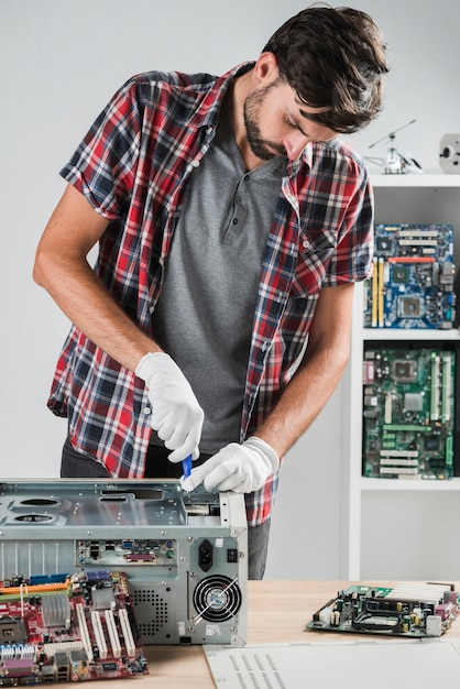 Young male technician working on computer cpu in workshop Free Photo