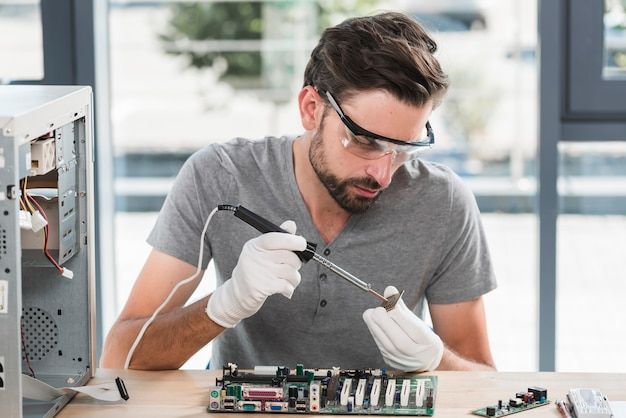 Young male technician working on computer ram Free Photo