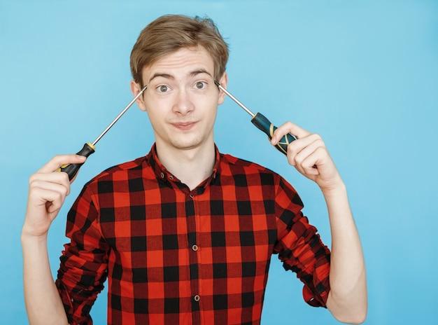 青い背景の上の赤いシャツの若い男性のティーンエイジャー Premium写真