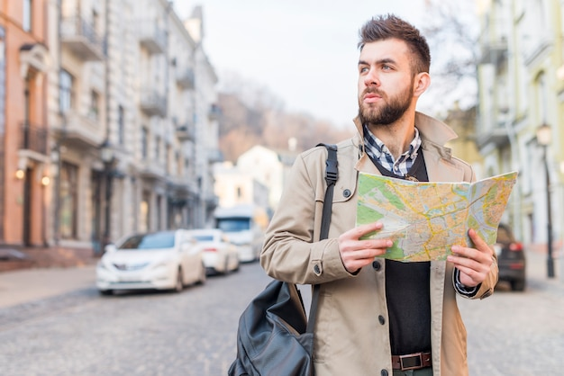Young male tourist with bag on his shoulder standing on street holding map in hand looking away Free Photo
