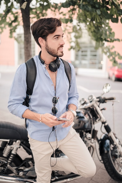 Young male tourist with smartphone standing in front of motorbike Free Photo