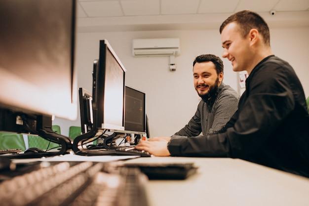 Молодые мужчины веб-дизайнеров, работающих на компьютере Бесплатные Фотографии