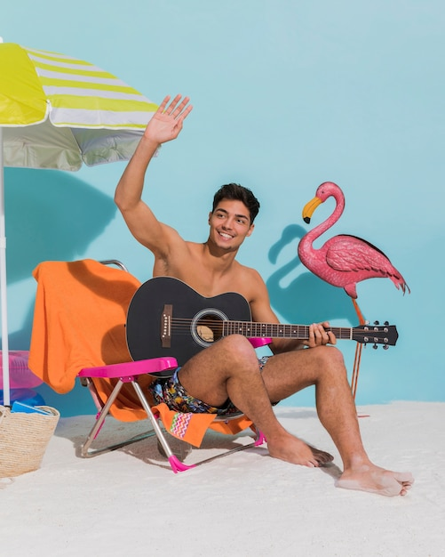 Young male with guitar waving hand on beach Free Photo