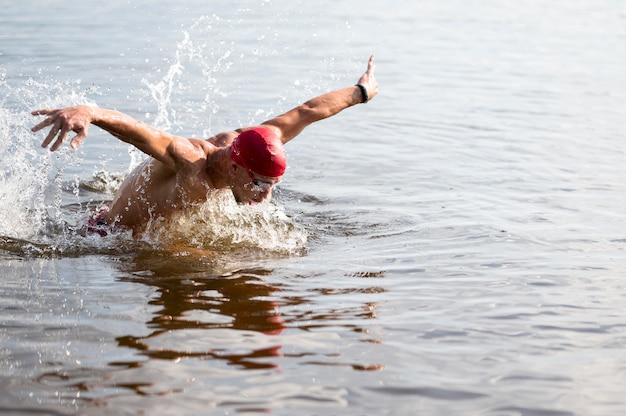 湖で泳いでいる赤い帽子の若い男性 無料写真