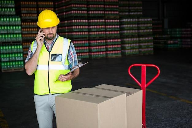 工場で電話で話している若い男性労働者 無料写真