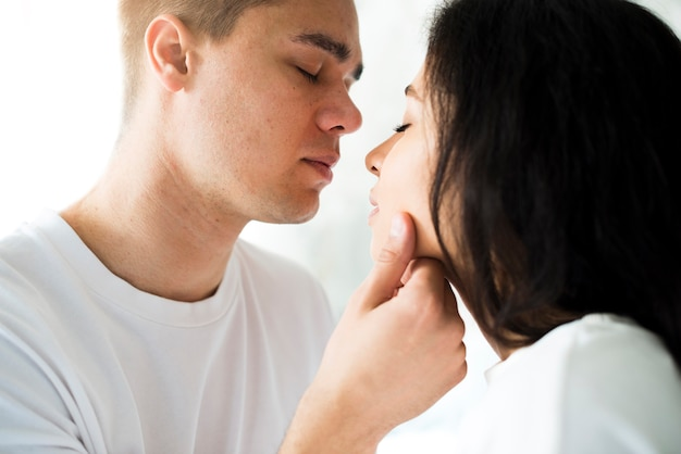 Young man about to kiss petty ethnic woman Free Photo