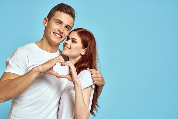 Молодая пара мужчина и женщина в белых футболках на голубом фоне Premium Фотографии