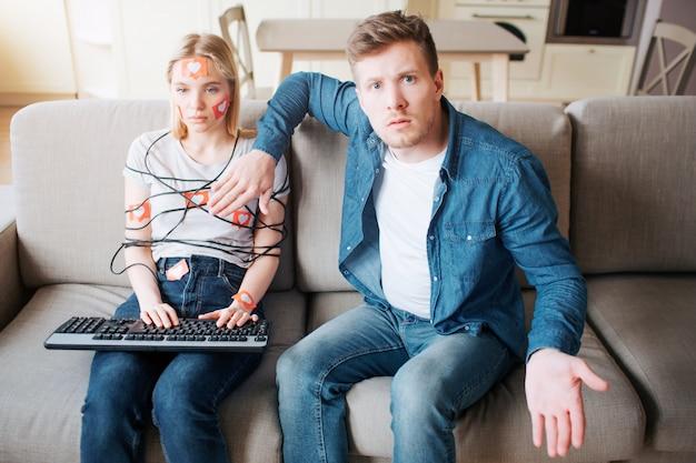 若い男と女はソーシャルメディア中毒です。ソファに座っています。人質。ソファの上の感情のない女性。カメラを探している心配している人。気が散る。 Premium写真