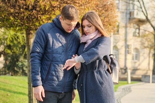 Молодой мужчина и женщина в городе, глядя на наручные часы Premium Фотографии