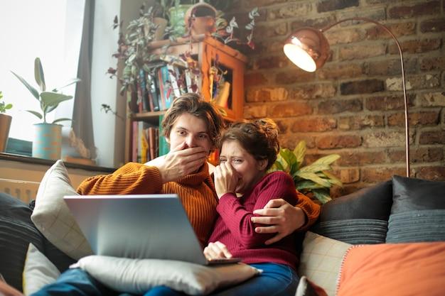 젊은 남자와 여자는 소파에 누워 노트북에서 공포 영화를보고 프리미엄 사진