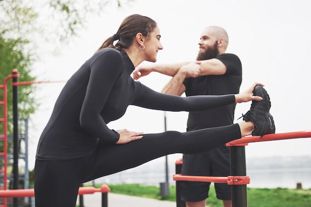 若い男性と女性はスポーツをする前に運動とストレッチマークを実行します 無料写真