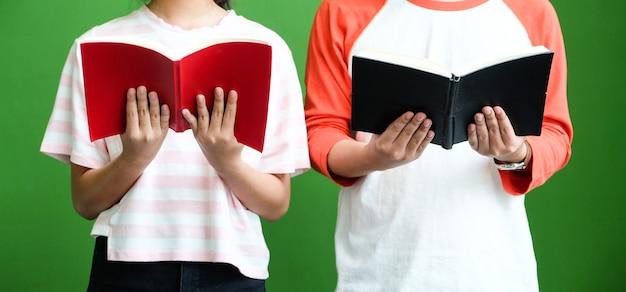 緑の壁の背景の前に立って、読書の若い男女の学生 Premium写真