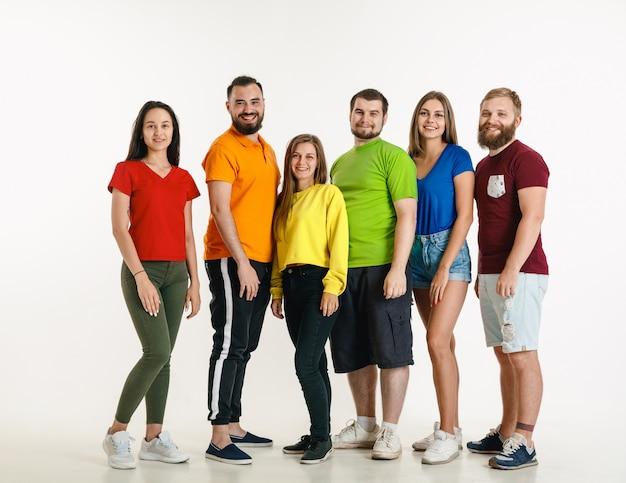 Молодой мужчина и женщина в цветах флага лгбт на белой стене. кавказские модели в ярких рубашках. выглядите счастливым, улыбающимся и обнимающимся. концепция гордости, прав человека и выбора лгбт. Бесплатные Фотографии
