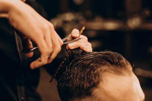 理髪店で髪をトリミングする若い男 無料写真