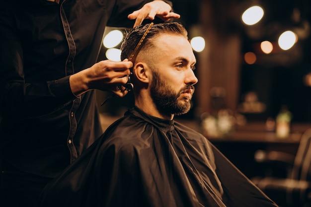 Молодой человек в парикмахерской, стригущий волосы Бесплатные Фотографии
