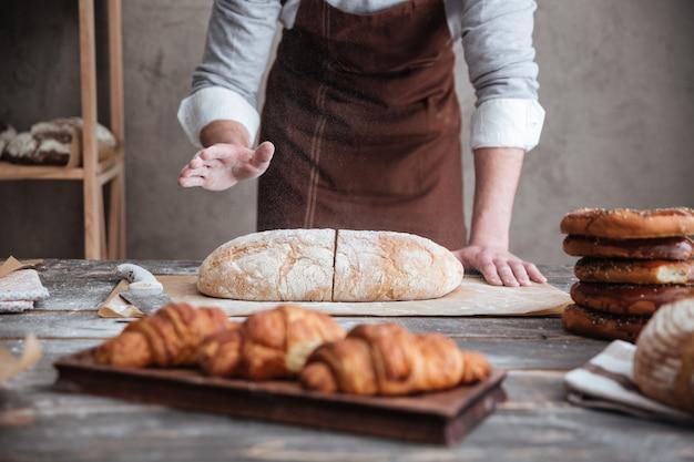 若い男のパン屋がパンを切った。 無料写真