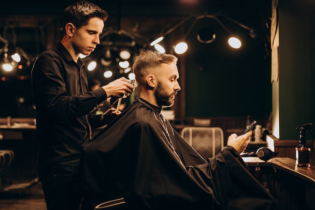 Young man at barbershop trimming hair Free Photo