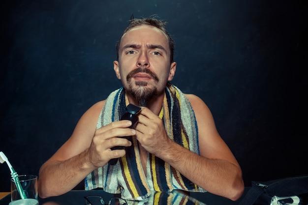 Giovane uomo in camera da letto seduto davanti allo specchio grattandosi la barba a casa Foto Gratuite