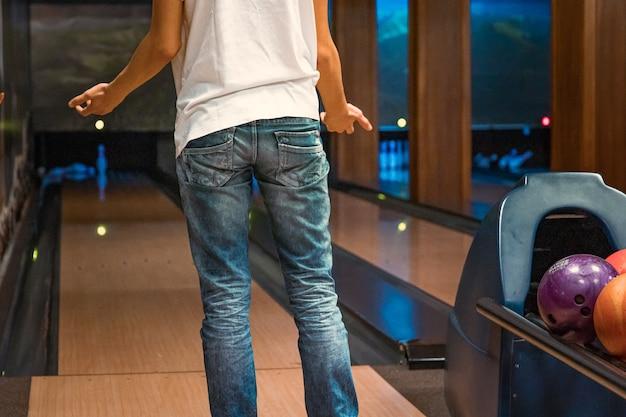 ボウリングのボールで悪いスローを怒っている若い男 Premium写真