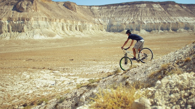 A young man on a bicycle is rolling from the mountain. slow motion Premium Photo
