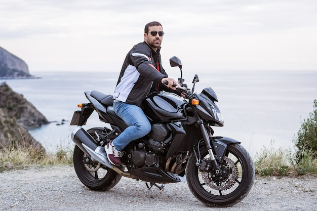 Young man biker with his black motorbike ready to drive, in front of the sea Premium Photo
