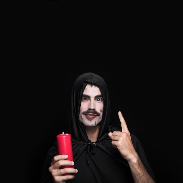 Young man in black cloak standing in studio with candle Free Photo